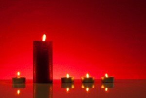 Five burning candles over red background